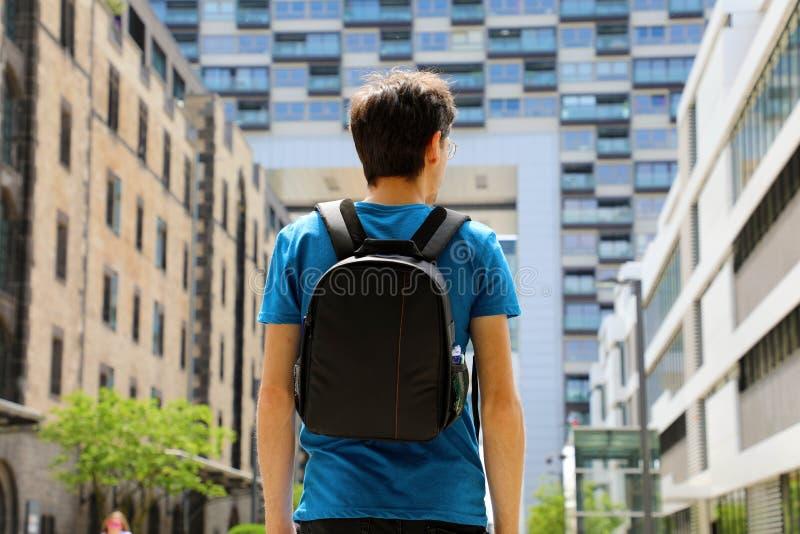 De achtermening van een jonge mens met rugzak kwam enkel in een grote stad en het kijken aan aan moderne gebouwen met perspectiev royalty-vrije stock foto