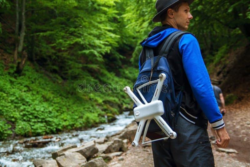 De achtermening van een reiziger met rugzakken en een helikopter bevindt zich voor een waterval royalty-vrije stock afbeeldingen