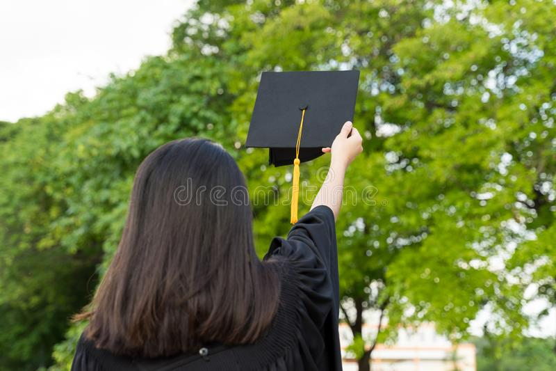 De achtermening van een vrouwelijke universitaire gediplomeerde bevindt zich en houdt graadcertificaat om in de graduatieceremoni stock foto