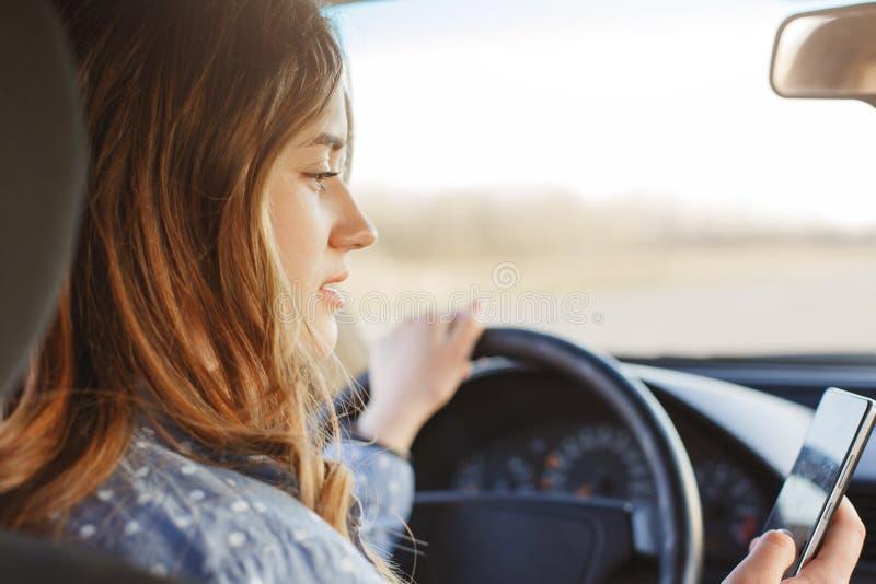 De achtermening van geconcentreerde vrouwelijke bestuurder zit in auto, houdt moderne celtelefoon, typt berichten of leest online royalty-vrije stock fotografie