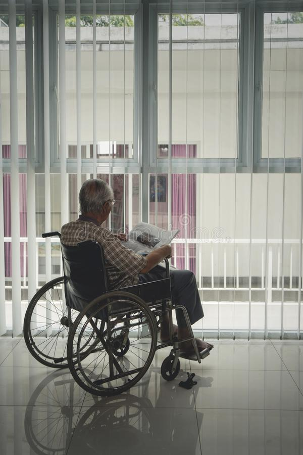 De achtermening van de gehandicapte hogere mens leest een krant stock foto's
