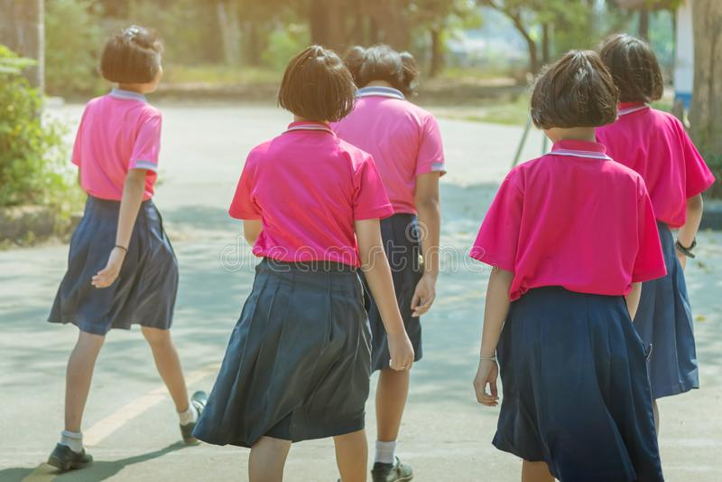 De achtermening van geluk primaire studentes in roze overhemd en de blauwe rok lopen aan klaslokalen stock foto's