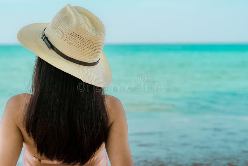 De achtermening van gelukkige jonge Aziatische vrouw in roze zwempak en strohoed ontspant en geniet van vakantie bij tropisch par royalty-vrije stock foto