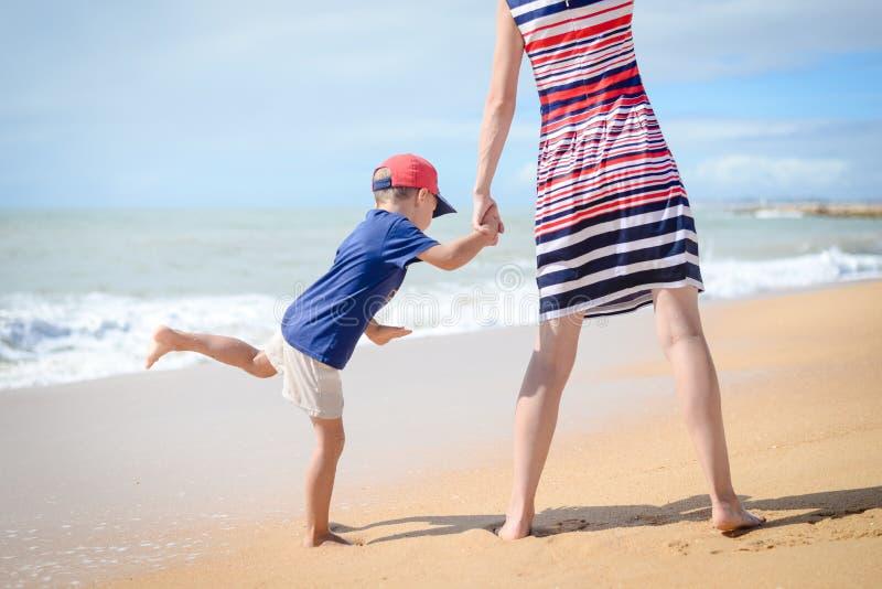 De achtermening van gelukkige opgewekte moeder en het jonge geitje hebben pret in openlucht op strand op zonnig stock afbeeldingen
