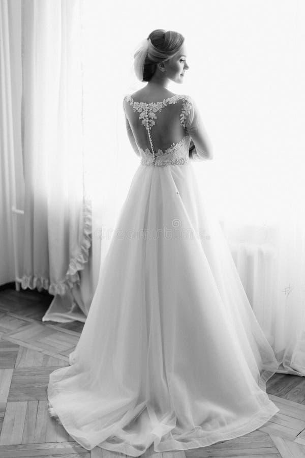 De achtermening van gemiddelde lengte van de bruid die zich dichtbij het venster bevinden Foto in zwarte kleuren royalty-vrije stock afbeeldingen