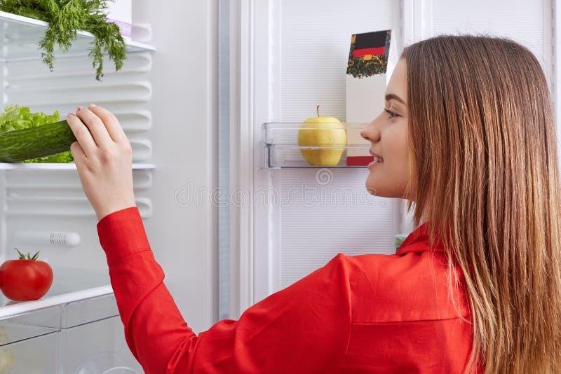 De achtermening van huisvrouw draagt rode blouse, bevindt zich voor geopende ijskast, kiest komkommer en tomaten voor het maken v stock fotografie