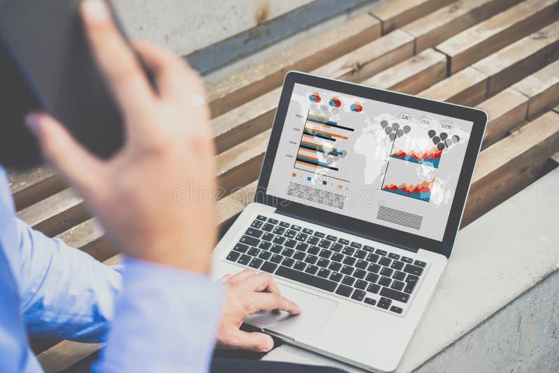 De achtermening van jonge zakenman zit binnen openlucht en gebruikt laptop met grafieken, diagrammen en grafieken op het scherm stock foto