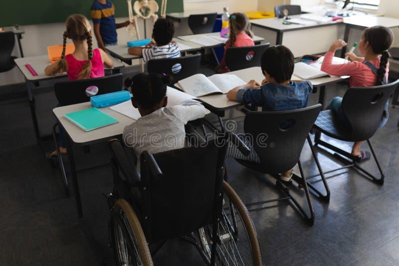 De achtermening van maakt schooljongen met klasgenoot het bestuderen en het zitten bij bureau in klaslokaal onbruikbaar royalty-vrije stock afbeeldingen