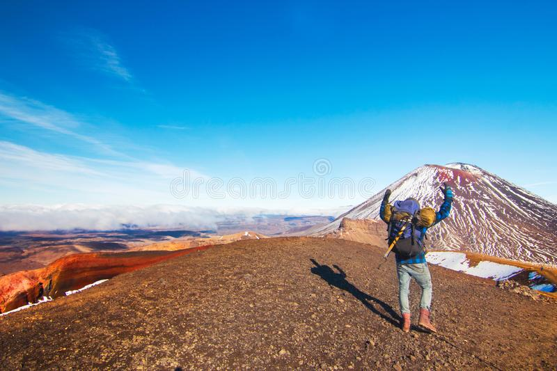 De achtermening van de mens, gelukkige reiziger en tramper in wilde bergen van vulkanisch landschap, klimmer bereikte hoge vlek,  stock afbeelding