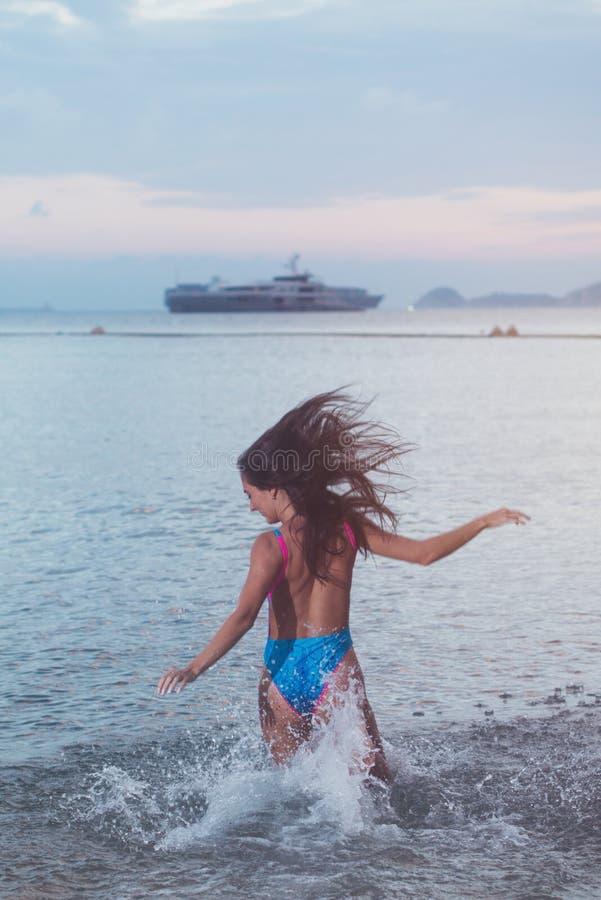 De achtermening van onbezorgde jonge vrouw met haar haar stroomde het runnen van in overzees bespattend water bij zonsondergang e stock foto's