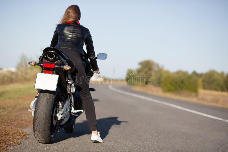 De achtermening van snelle vrouwelijke motorrijder draagt leerjasje, stelt op motor, neemt onderbreking na het rennen competities stock afbeeldingen