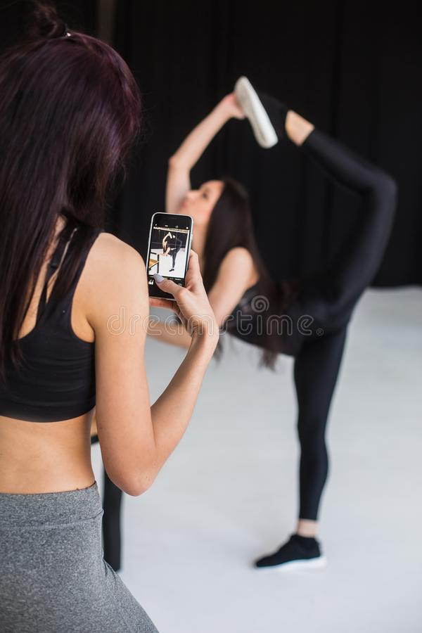 De achtermening van de sportenvrouw die foto van het vage atletische meisje in nemen stelt van bevindende boog De mening van royalty-vrije stock foto's