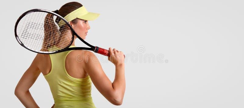 De achtermening van sportief wijfje houdt van tennis, houdt racket, draagt toevallige t-shirt en GLB, klaar om, tribunes met wh t stock fotografie