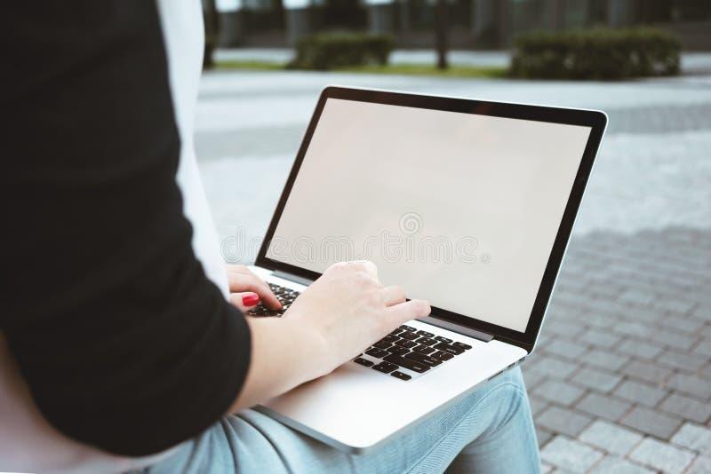 De achtermening van studente is het werk aangaande laptop toetsenbord in openlucht in stedelijk royalty-vrije stock fotografie