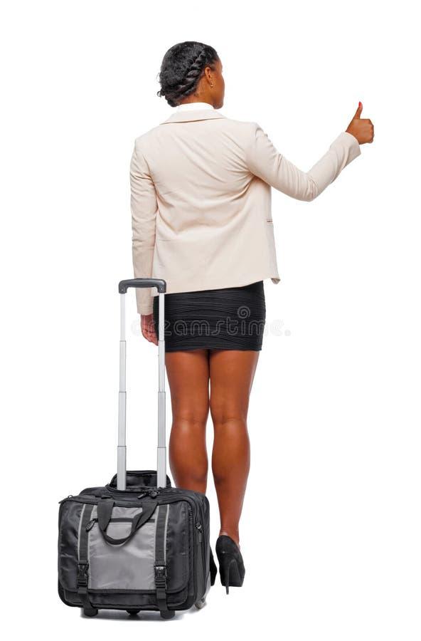 De achtermening van stylishly gekleed bedrijfszwarte met koffer toont duim royalty-vrije stock fotografie