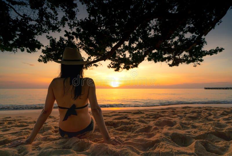 De achtermening van zwangere vrouw zit op zand en het letten op zonsondergang bij tropisch strand Het zwempak en het strohoed van stock fotografie