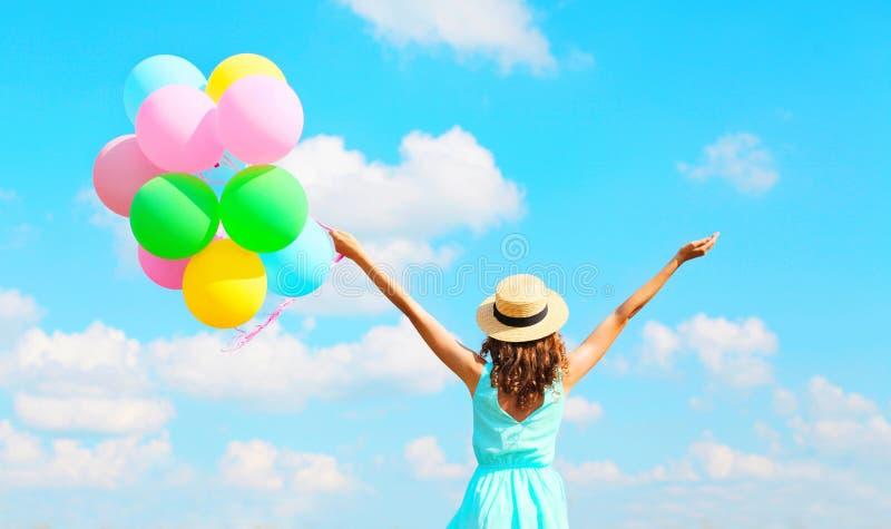 De achtermenings gelukkige vrouw met een lucht kleurrijke ballons geniet van een de zomerdag op blauwe hemelachtergrond royalty-vrije stock foto