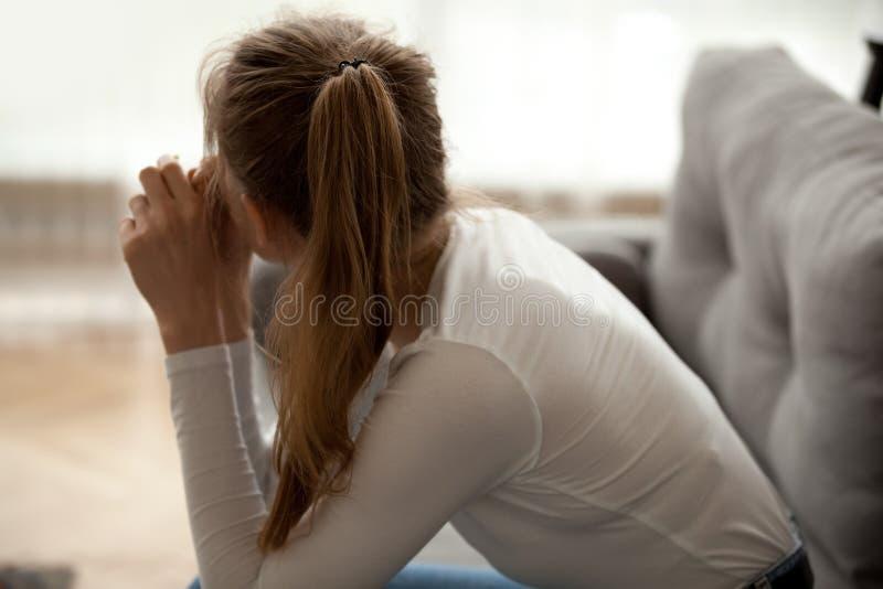 De achterzitting van de menings peinzende nadenkende die vrouw op bank, in gedachten wordt verloren stock foto