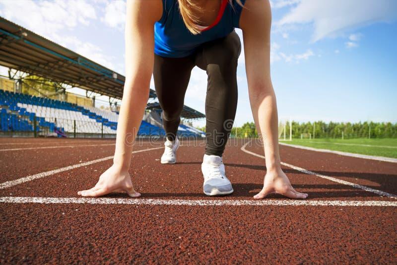 De actie pakte beeld van een vrouwelijke atleet in die die de startblokken voor een sprint verlaten op een spoor in werking wordt royalty-vrije stock foto