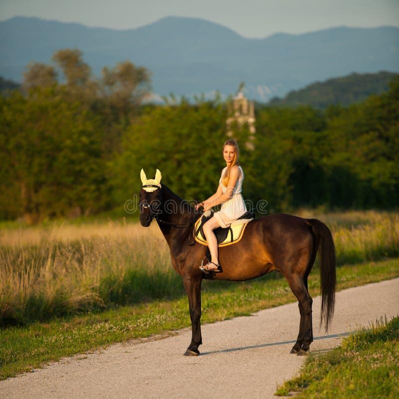 De actieve jonge vrouw berijdt een paard in aard stock foto