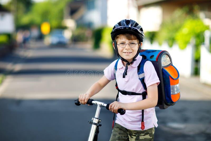 De actieve jongen van het schooljonge geitje in veiligheidshelm het berijden met zijn autoped in de stad met rugzak op zonnige da stock afbeeldingen
