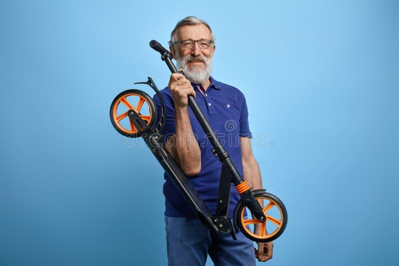 De actieve knappe oude mens in modieuze vrijetijdskleding gaat autoped berijden stock foto's