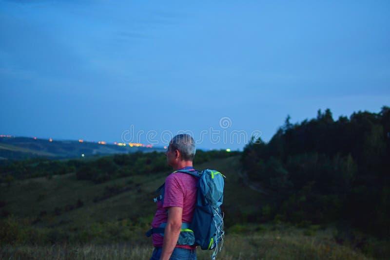 De actieve midden oude mens die zich op heuvel met rugzak bevinden, geniet van bekijkend bergenlandschap tijdens schemering stock fotografie