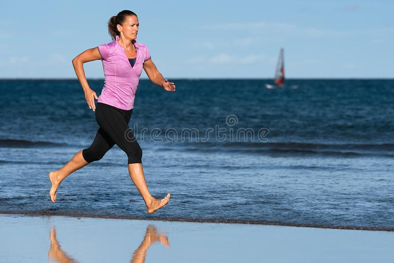 De actieve sportieve vrouw stelt het lopen op het strand in werking royalty-vrije stock foto's