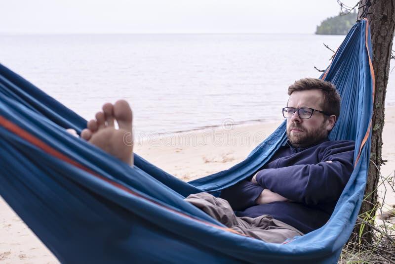 De actieve toerist is ernstige dromen en nadenkend terwijl hij in een hangmat rust stock fotografie