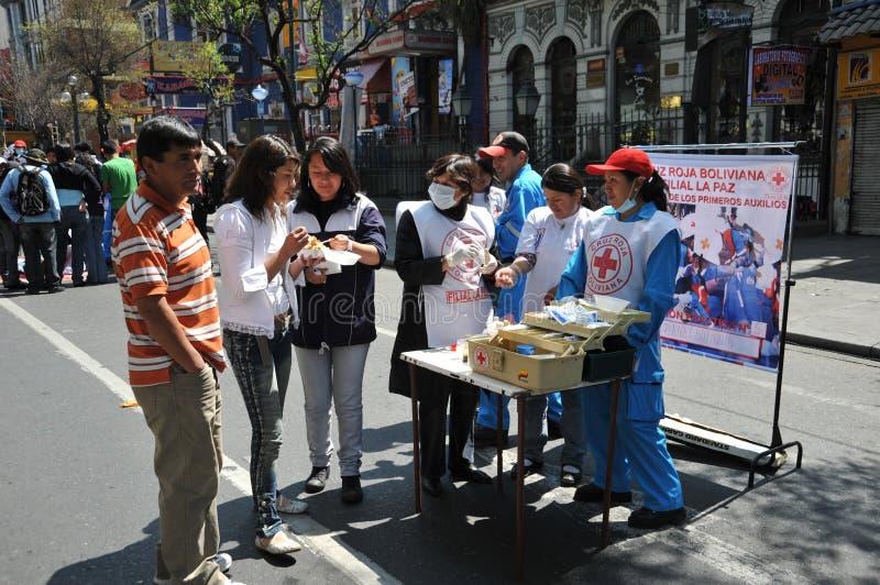 De activisten van het rode kruis onderwijzen menseneerste hulp op een stadsstraat stock afbeelding