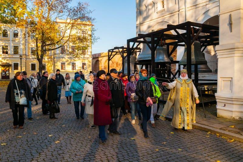 De actrice en de toeristen van de reisgids bij de excursie bij het grondgebied van het park van Novgorod het Kremlin, Veliky Novg royalty-vrije stock fotografie