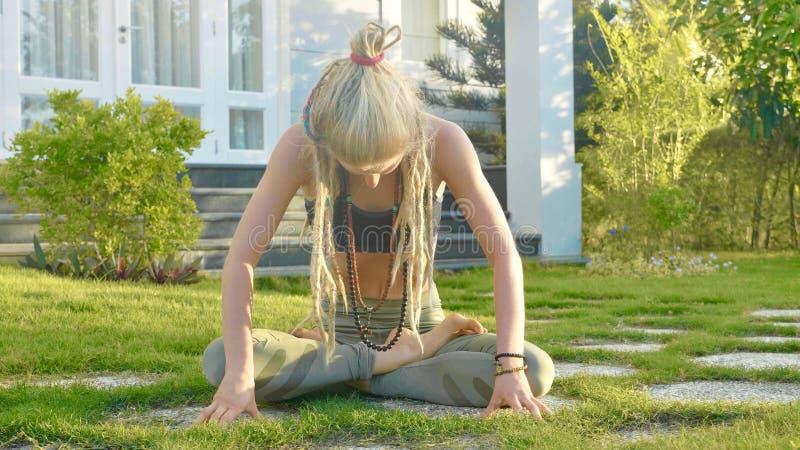 De ademoefening van de Pranayamayoga door een jonge vrouw in de binnenplaats van haar huis stock afbeelding