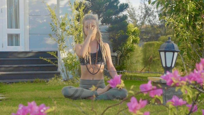 De ademoefening van de Pranayamayoga door een jonge vrouw in de binnenplaats van haar huis stock fotografie
