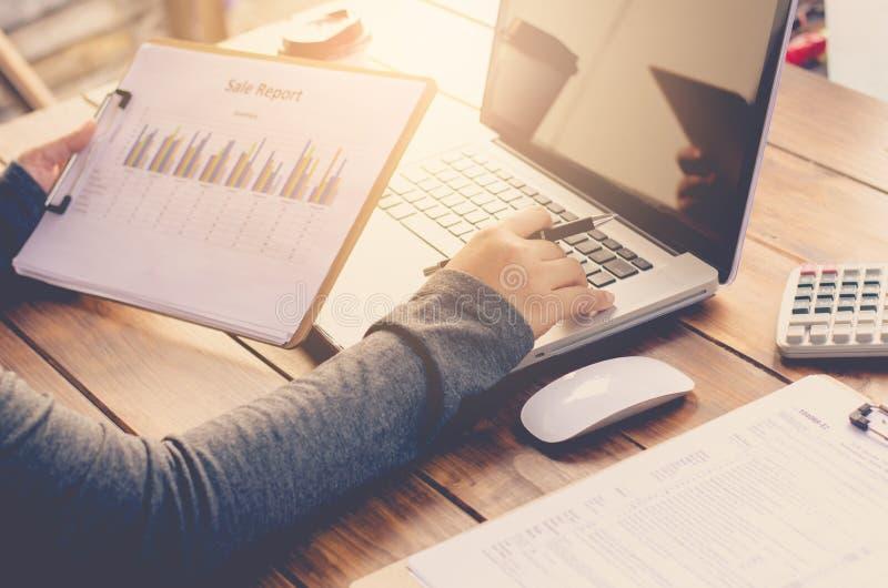 De administratie van de zakenmanholding op de lijst en het analyseren van investeringsgrafiek die in bureau werken Bedrijfs het w stock foto