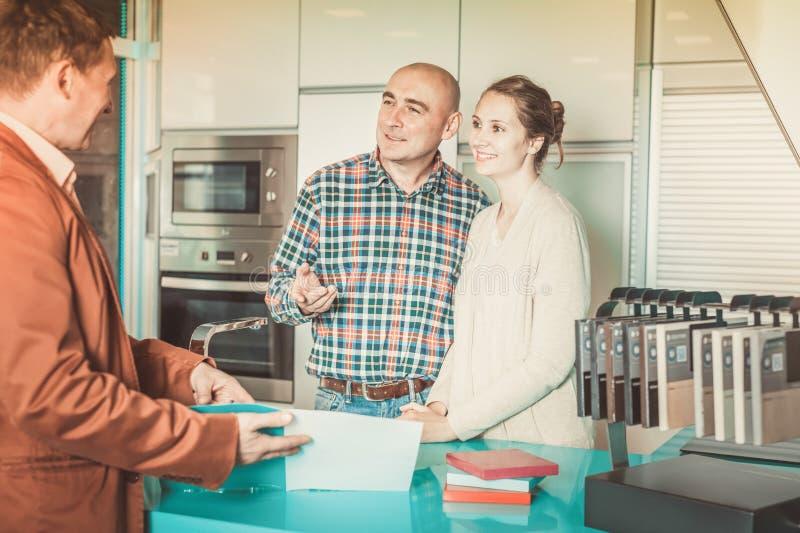 De adviseur biedt om keukenmeubilair te bekijken aan stock fotografie