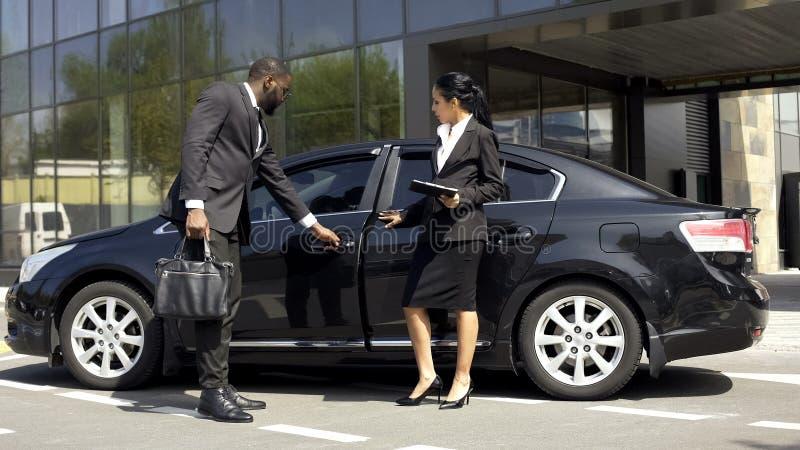 De adviseur die van de autotoonzaal luxeauto tonen aan koper, voertuig die zaken huren stock afbeelding