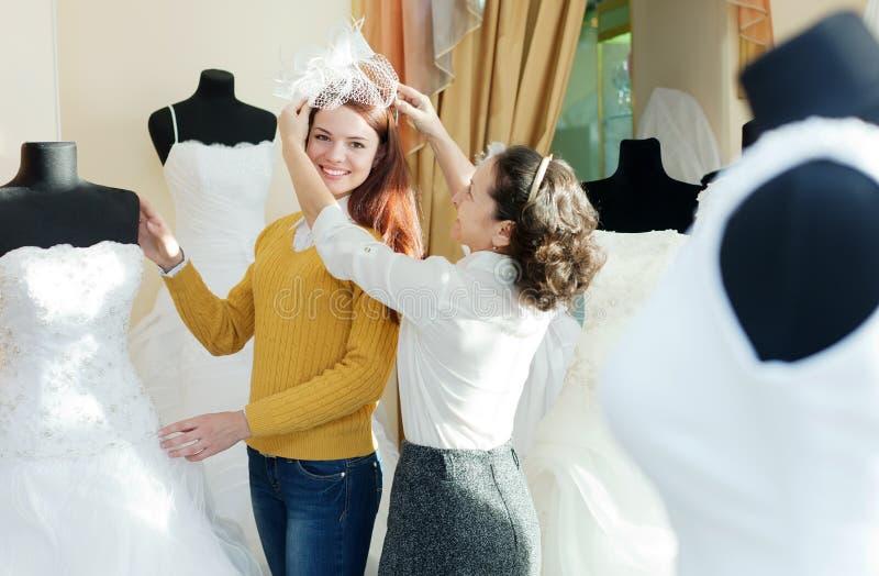 De adviseur helpt meisje kiest witte bruids uitrusting royalty-vrije stock afbeeldingen