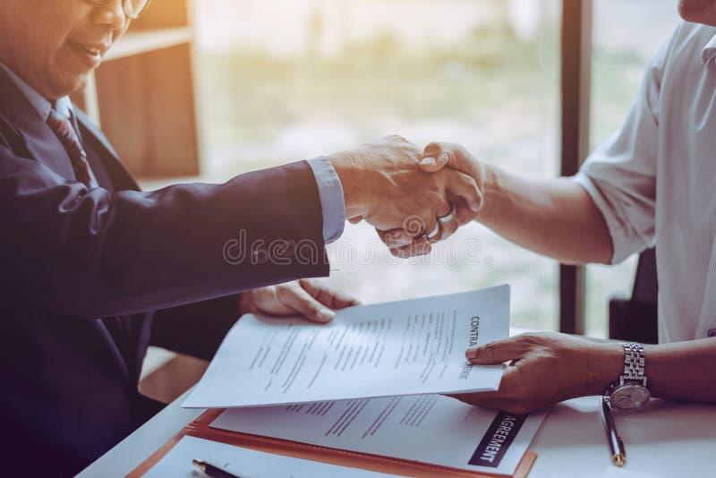 De advocatenprocureurs die van de middenleeftijds Aziatische partner handen na het bespreken van een gedaane contractovereenkomst stock foto