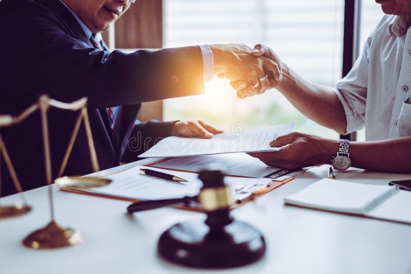 De advocatenprocureurs die van de middenleeftijds Aziatische partner handen na het bespreken van een gedaane contractovereenkomst royalty-vrije stock afbeelding