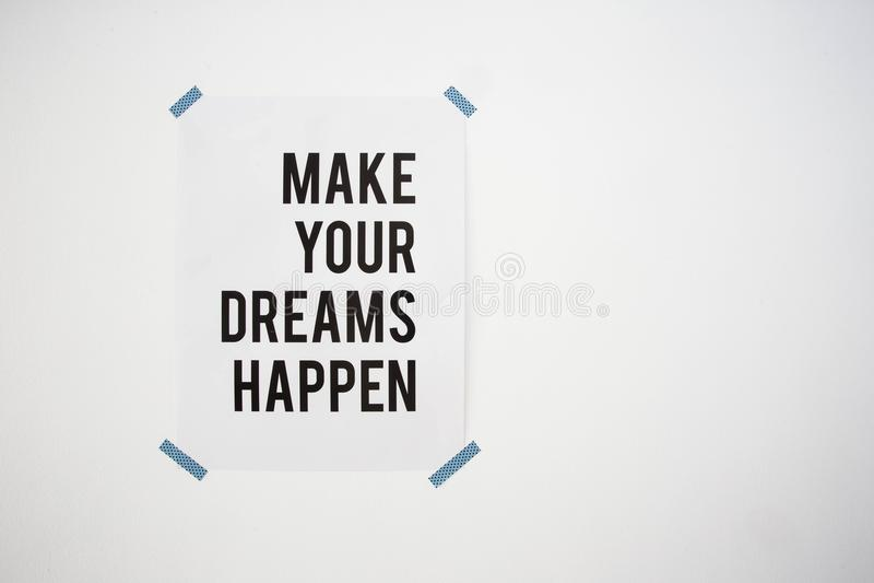 De affiche op witte muur met het citaat maakt uw dromen abstracte gebeuren textuur als achtergrond stock foto