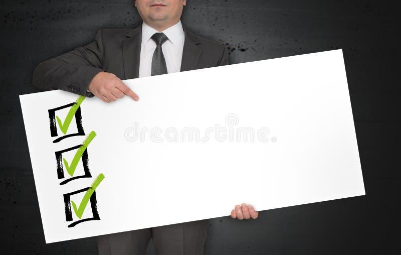 De affiche van het controlelijstmalplaatje wordt gehouden door zakenman stock fotografie