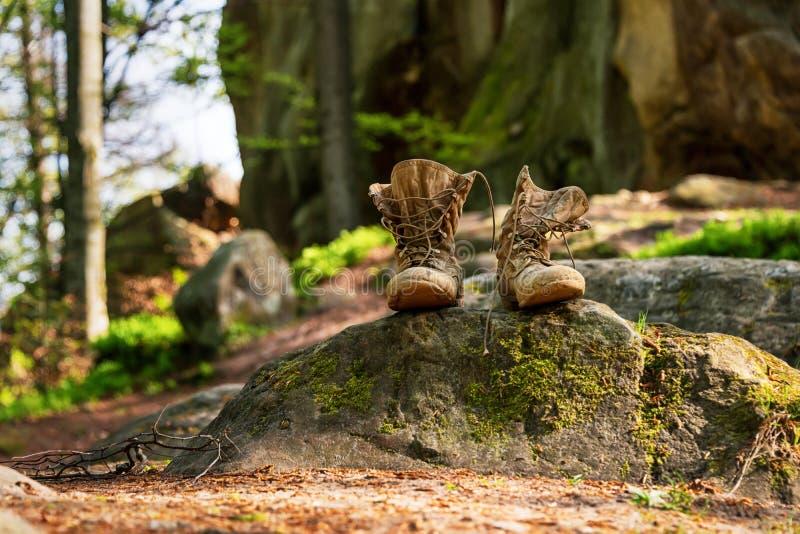 De afgezaagde wandelingslaarzen, unlaced en modderig op de bosvloer Het concept van het toerisme stock foto's