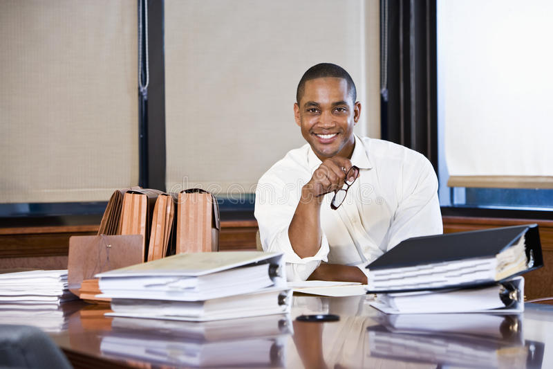 De Afrikaanse Amerikaanse documenten van de zakenmanlezing royalty-vrije stock foto's