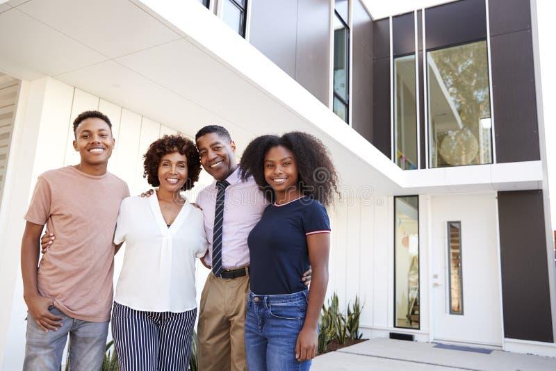 De Afrikaanse Amerikaanse familietribune die aan camera voor hun modern huis kijken, sluit omhoog royalty-vrije stock afbeeldingen