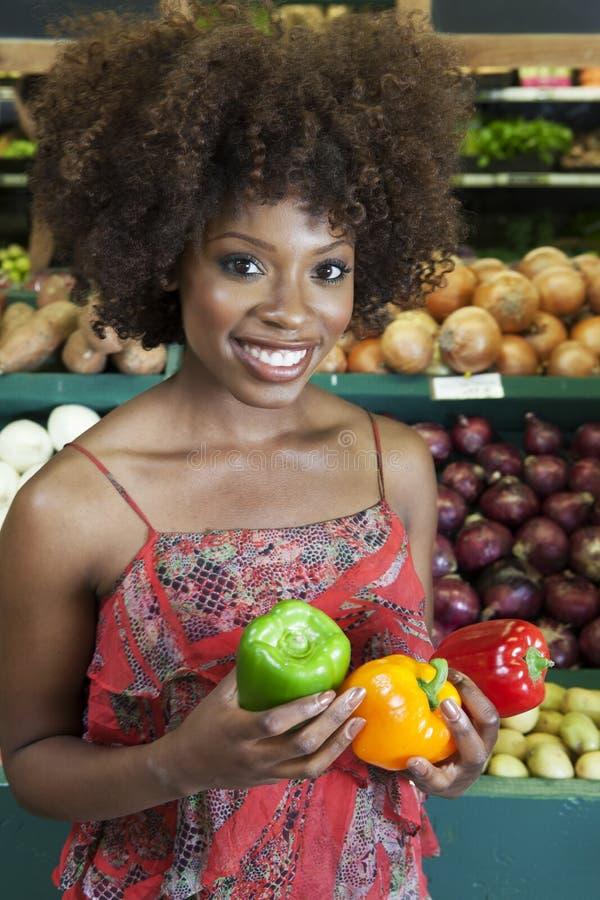 De Afrikaanse Amerikaanse groene paprika's van de vrouwenholding bij supermarkt royalty-vrije stock fotografie