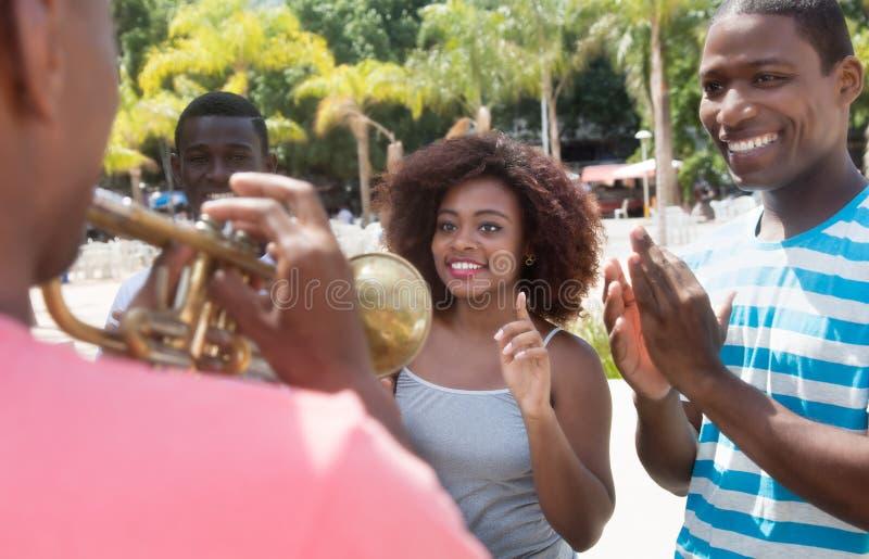 De Afrikaanse Amerikaanse groep geniet van muziek van musicus met trompet stock afbeelding