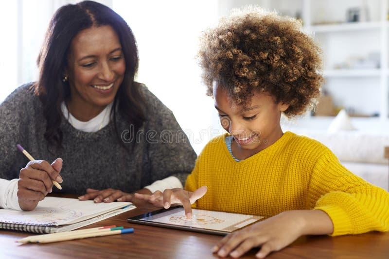 De Afrikaanse Amerikaanse jonge grootmoederzitting bij lijst die thuiswerk met haar kleindochter doen die een tabletcomputer met  stock afbeeldingen