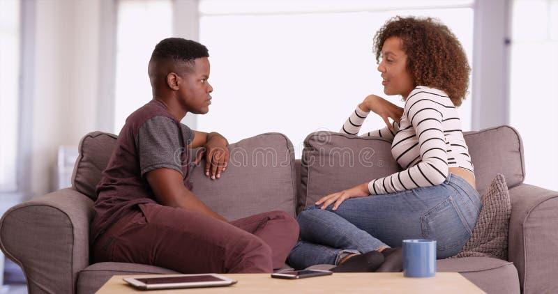 De Afrikaanse Amerikaanse man en de vrouw spreken terwijl het ontspannen op hun laag in hun woonkamer royalty-vrije stock afbeeldingen