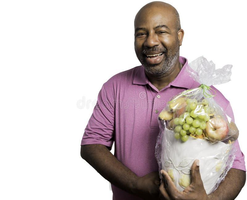 De Afrikaanse Amerikaanse Mens houdt cheerfully een fruitmand op witte achtergrond stock afbeelding