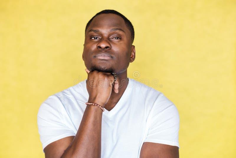 De Afrikaanse Amerikaanse mens zette zijn kin op zijn handen en kijkt zorgvuldig stock foto